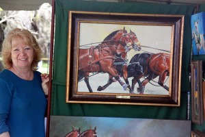 Equestrian artist Moe Hahn shows off a completed painting of Chester Weber's winning four-in-hand team.