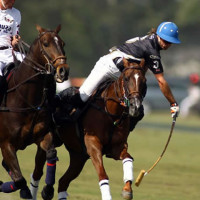 Piaget's Sapo Caset leans out of the saddle to keep possession of the ball on a run downfield, with Polito Pieres of Lechuza Caracas closely defending